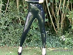 Outdoor latex babe Olivias high heels and shiny rubber fetish wear of posing solo softcore brunette teen beauty
